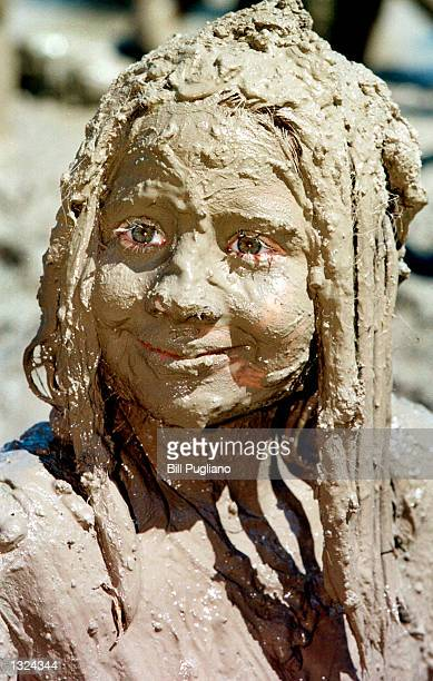 Sevenyearold Neva Powell of Romulus Michigan plays in mud while celebrating Mud Day July 10 2001 in Wayne Michigan