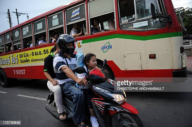 Sevenyearold Thai student Chamaya Pamutito rides a scooter as she travels back from school along with her father and mother in Bangkok on June 6 2013...