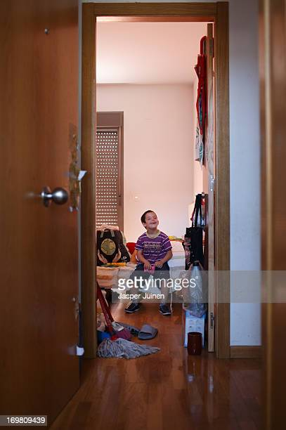 Sevenyearold Yeray Laguna Arias who has Down syndrome and was evicted from his home with his parents and twin sisters almost a year ago sits on his...