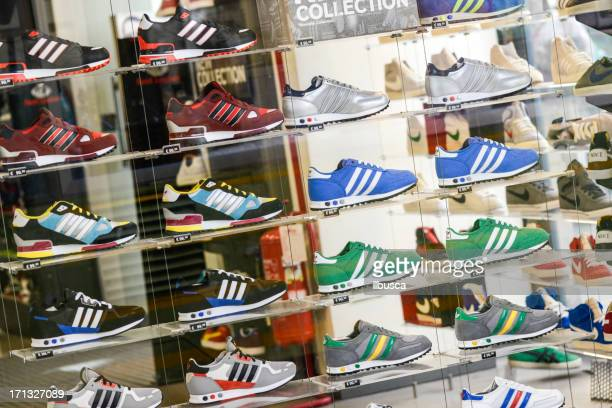 Several Adidas shoes in Foot Locker store window