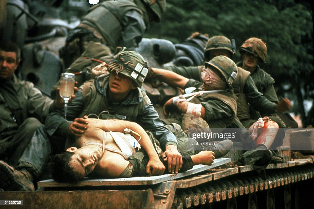Several bloody and bandaged soldiers ride on top of a tank used as a make-shift ambulance after the Battle of Hue in the Vietnam War, Hue, Vietnam, February 15, 1968.