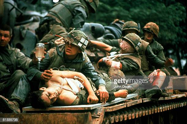 Several bloody and bandaged soldiers ride on top of a tank used as a makeshift ambulance after the Battle of Hue in the Vietnam War Hue Vietnam...