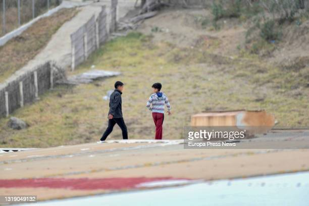 Several boys walk on a roof while trying to escape from the first reception building in the Tarajal industrial estate, on 20 May, 2021 in Ceuta,...