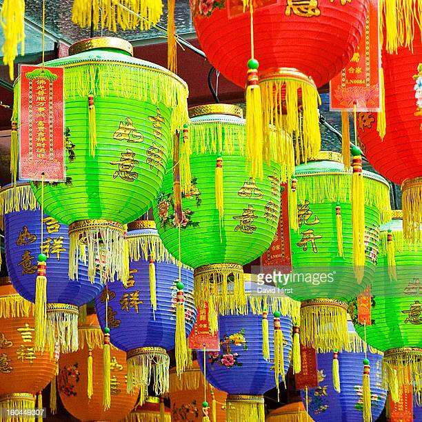 CONTENT] several bright and colourful chinese lanterns hanging in rows in singapore outside a temple