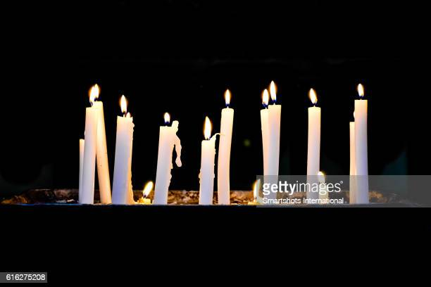 several candlelights lit up against black background - religious service stock pictures, royalty-free photos & images
