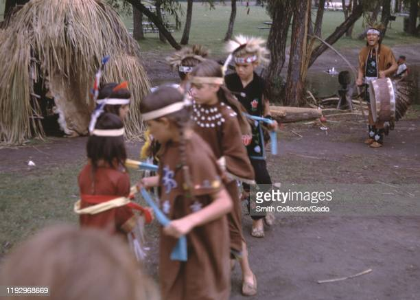Several Caucasian children wearing Native American style costumes and play among tepees outdoors, suggesting the children's game Cowboys and Indians,...