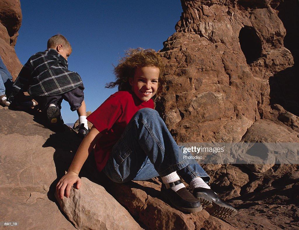 Several caucasian kids climb upon redrock : Stockfoto