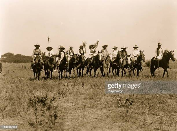 Several Cheyenne chiefs on horseback in a row in an open field