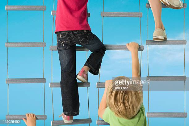 Several children going up hanging stairs in a race