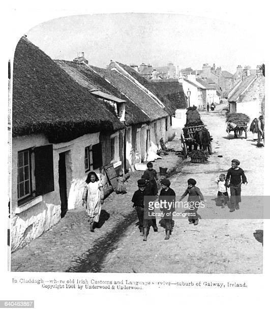 Several children walk down a street in Claddagh a suburb of Galway Ireland ca 1901