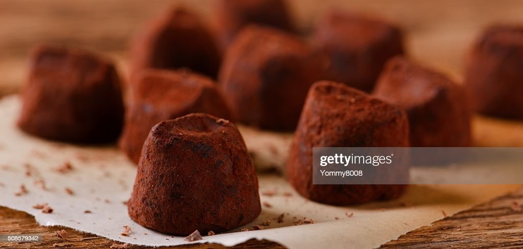 Several chocolate truffles on piece of paper : Stock Photo