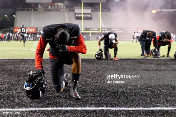 Several Cincinnati Bearcats players kneel to pray in the end zone prior to the start of the game against the East Carolina Pirates at Nippert Stadium...