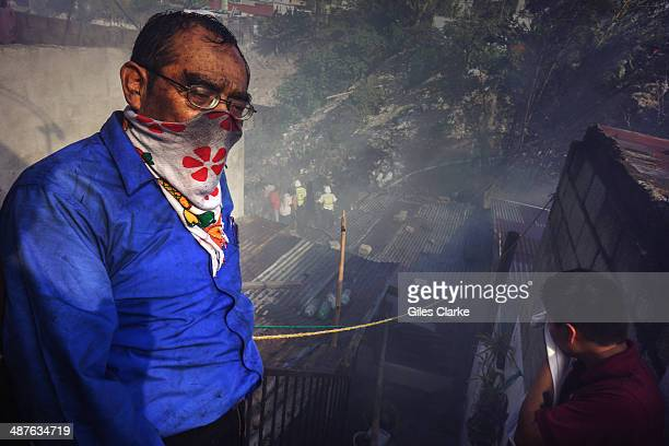 Several civilians watch volunteer firefighters rush to the scene of a canyon fire January 18 2014 in Guatemala City Guatemala The bomberos...