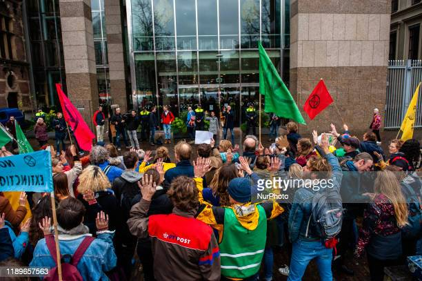 Several climate activists are gathered in front of the Tweede Kamer during a demonstration in support of the Urgenda case that took place in front of...