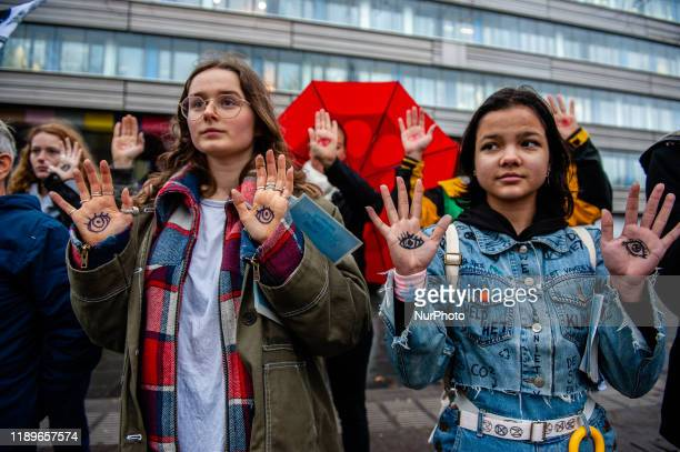 Several climate activists are showing their hands with eyes painted on them during a demonstration in support of the Urgenda case that took place in...