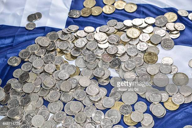several coins of old Drachmas on a Greek flag