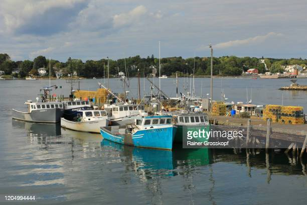 several colorful fishing boats at the commercial fishing pier on peirce island - rainer grosskopf stock-fotos und bilder