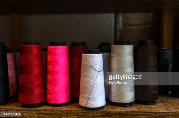 several colorful line reels, on shelf of fixtures - polyester stock photos and pictures