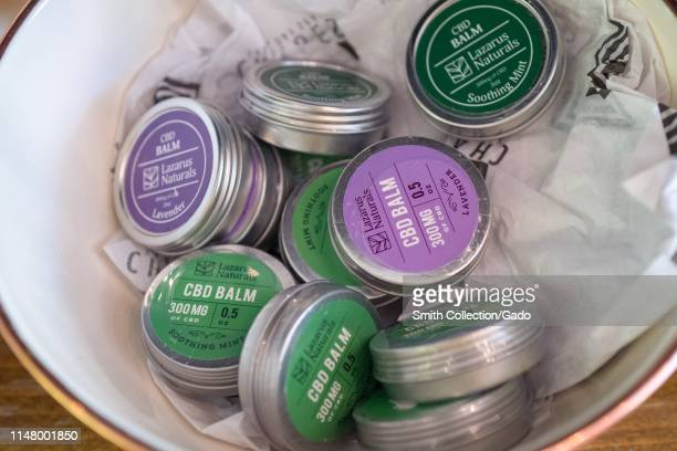 Several containers of lip or skin balm containing Cannabidiol or CBD derived from the Cannabis plant are displayed on the shelf of a store in Walnut...