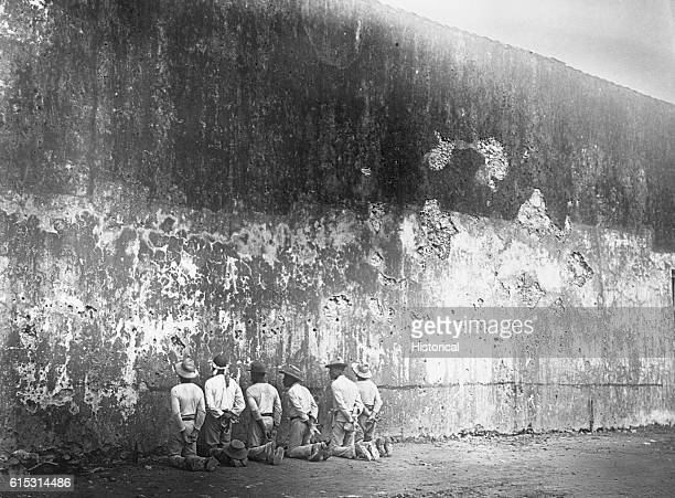 Several Cuban men kneeling along a wall await execution by firing squad in Santiago during the SpanishAmerican War