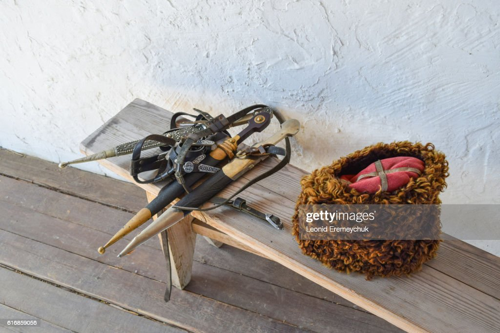 Several daggers on a bench near a Cossack hat : Stock Photo