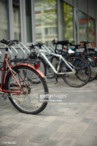 several different bikes parked by a building in a parking lot - kristina strasunske stock photos and pictures