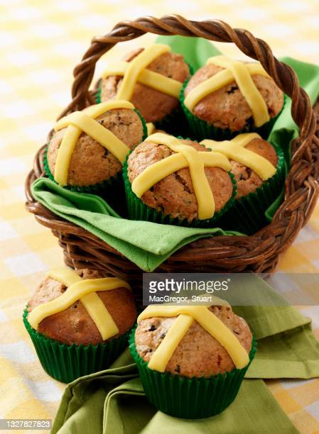 several easter muffins with marzipan crosses in a basket and on a napkin sitting on a gingham cloth - marzipan stock pictures, royalty-free photos & images