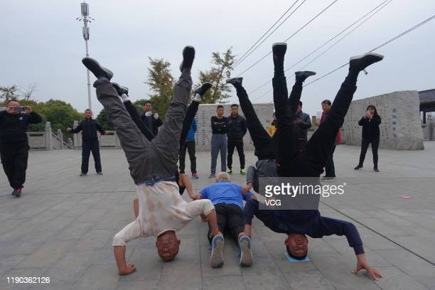 Several elderly people with an average-aged of 55 do headstands near the Quan River on November 21, 2019 in Fuyang, Anhui Province of China.