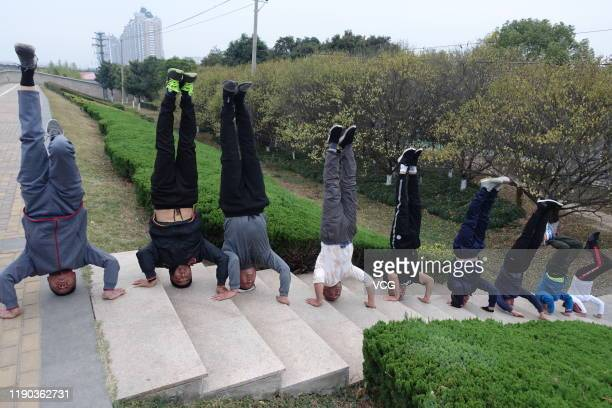 Several elderly people with an averageaged of 55 do headstands near the Quan River on November 21 2019 in Fuyang Anhui Province of China