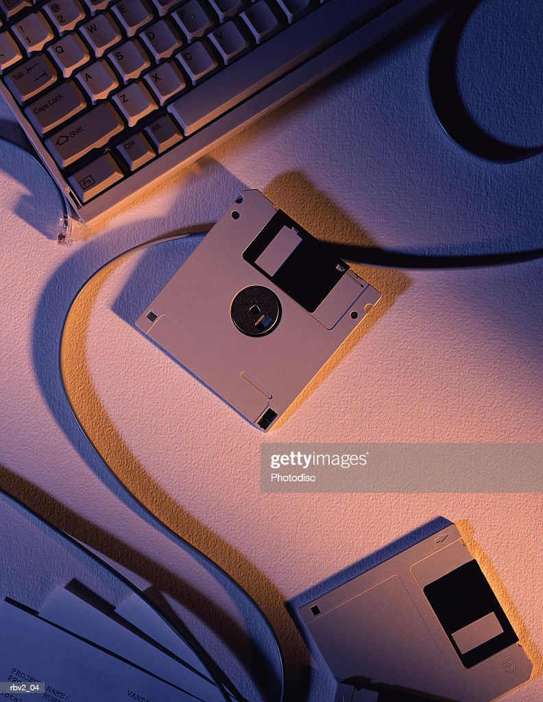 Several floppy disks sit on a table next to papers and a computer keyboard as light casts shadows : Foto de stock