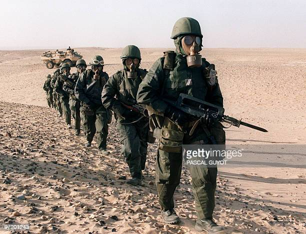Several gas-masked French soldiers from the Foreign Legion Infantry regiment practice 23 October 1990 in the Saudi desert near Hafr al-Baten, NBC...