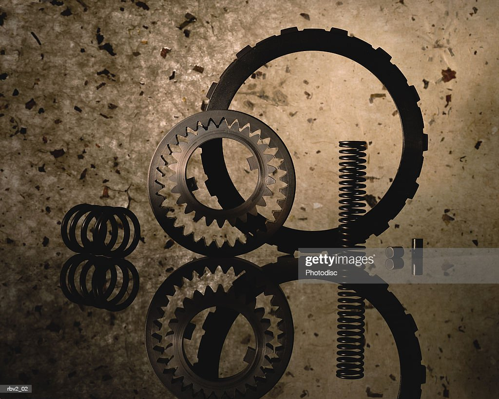 several gears and a spring stand on a reflective surface with a speckled background : Foto de stock