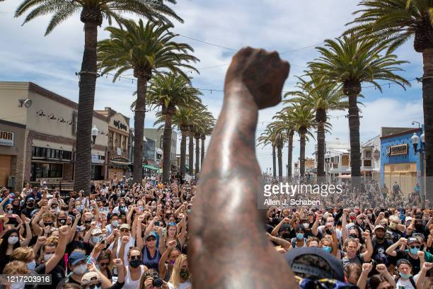 Several hundred Black Lives Matter protesters take a knee and hold their fists in the air during a moment of silence to honor George Floyd during a...