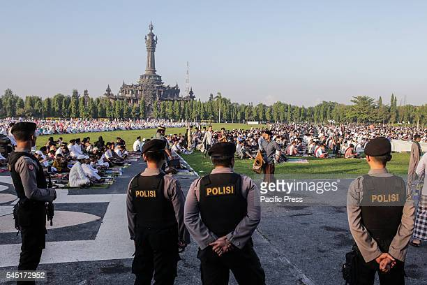 MONUMENT DENPASAR BALI INDONESIA Several Indonesian armed police stand guard as hundreds of Muslims take part during Eid alFitr celebration pray at...