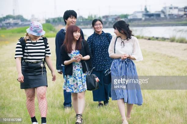 several japanese college students walk along the river - travel ストックフォトと画像