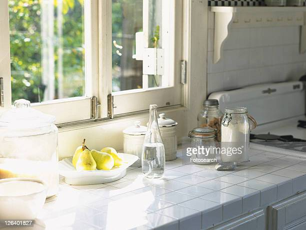 Several Kitchen Items, Such as Bottles and Tins Next to a Window, Side View