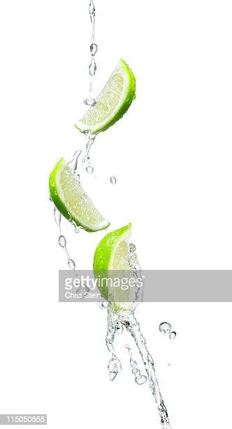 Several limes in a water splash