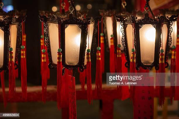 several lit lanterns hanging at the man mo temple in hong kong, china. - man motempel stockfoto's en -beelden