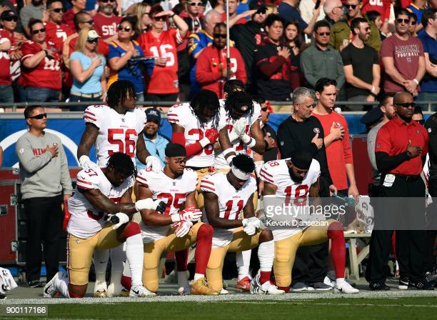 Several members of the San Francisco 49ers kneel during the anthem prior to the football game against Los Angeles Rams at Los Angeles Memorial...