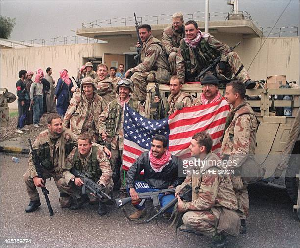 Several members of the US Special forces holding a US flag celebrate their victory over Iraqi army 27 February 1991 in Kuwait City Allied forces...