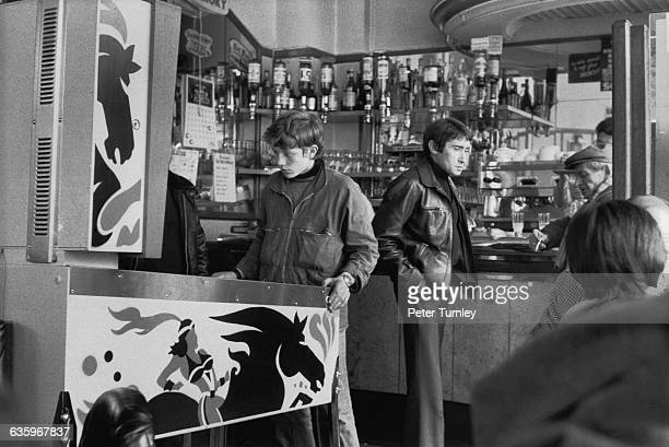 Several men drink and play pinball in a Paris cafe