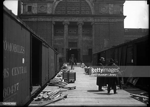Several men on wood loading dock for railroad car moving exhibit cases down ramp to be loaded Either west or east side of building a small part of...