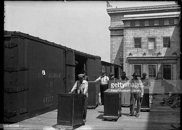 Several men outside of the new Field Museum building train with and 'Automobile' painted on the side loading dock Museum move series Chicago Illinois...
