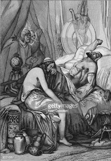 Several men peer through a curtain at the body of Attila king of the Huns which lies on a bed while his wife of one night Ildico weeps at his feet...