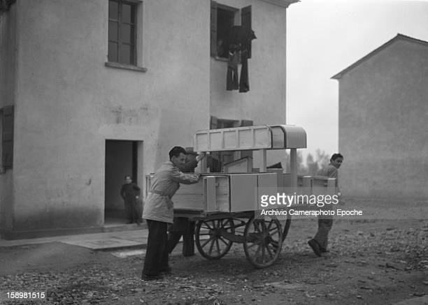 Several men use a cart of to move furniture along an unpaved street Venice Italy 1946