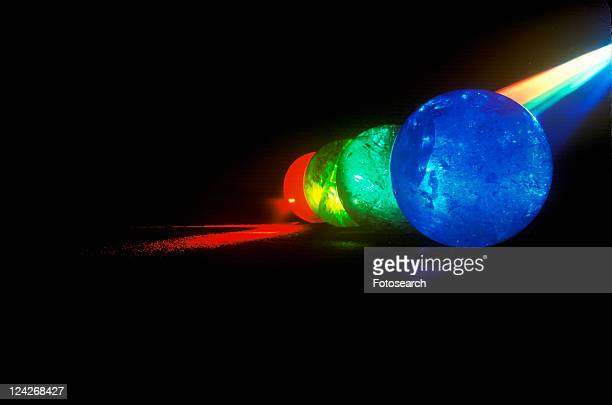 Several multi-colored spheres appearing as planets with laser lights shining through