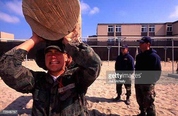 Several Navy Seal trainees haul a huge log in punishment for not having completed a previously assigned task to their officer's approval in this...