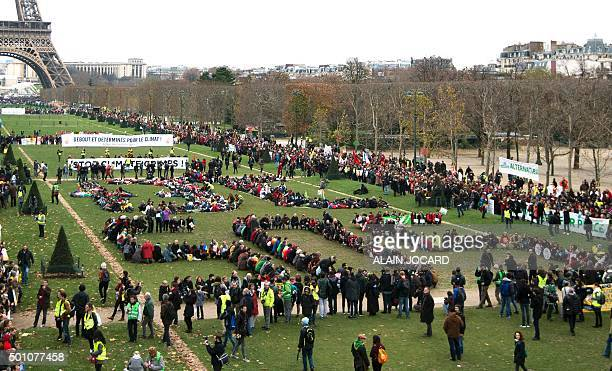 Several Non Governmental Organisations gather to form a human chain reading '3°C SOS' on the Champs de Mars near the Eiffel Tower on December 12 2015...