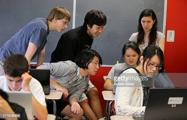Several pairs of eyes are on the screen of Erica Yuen, center right. Peering at the code are, clockwise from center: Richard Cui, Will Becker, Matt...