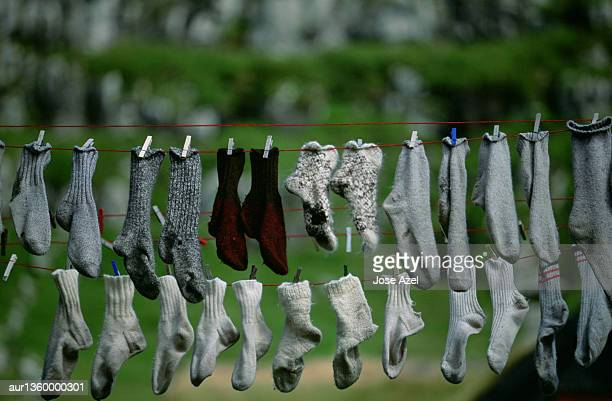 Several pairs of socks hang outside to dry on a clothes line, Faeroe Islands, Europe.